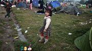 Une petite fille traîne son jouet parmi les abris de fortune
