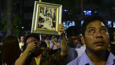 De nombreux thaïlandais brandissent des portrait du Roi devant l'hôpital où il est décédé