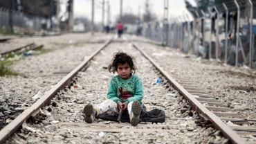 Une enfant joue sur les rails qui longent le camp de fortune dans lequel s'entassent des réfugiés piégés par la fermeture de la route des Balkans, près du village d'Idomeni, à la frontière entre Grèce et Macédoine