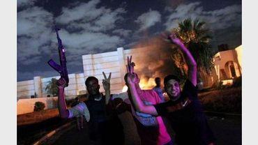 Des Libyens devant la caserne en feu du groupe salafiste d'Ansar al-Charia, à Benghazi, le 21 septembre 2012
