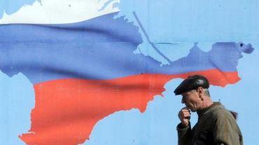 Un homme passe devant une affiche représentant la Crimée sous les couleurs de la Russie, à Sébastopol le 13 mars 2014