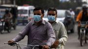 Les banlieusards portent des masques faciaux dans une rue de Karachi le 28 février 2020 alors que le Pakistan a détecté ses deux premiers cas de nouveau coronavirus. Les autorités pakistanaises se sont précipitées le 27 février pour dépister des centaines de personnes récemment arrivées d'Iran, qui est devenu un haut lieu majeur du coronavirus, après qu'Islamabad a confirmé ses deux premières infections.