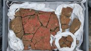 Les enduits déposés, ils révèlent leur décor, en grands panneaux rouges et inter-panneaux noirs, aux candélabres très raffinés, correspondant à un registre décoratif très présent en Gaule au Ier siècle de notre ère.