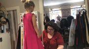 Evelyne fait un ourlet à la robe d'Alix