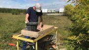 Michel Woodbury passe la terre et les gravats au tamis pour repérer les morceaux de silex, d'ossements ou de céramique.