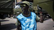 Un chauffeur de Forces Armées de la République Démocratique du Congo debout devant des camions militaires alignés le long du Boulevard du 29 octobre