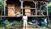 Philippe devant sa magnifique cabane construite en quelques semaines avec les matériaux donnés par la forêt.