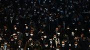 Les navetteurs vêtus de masques se rendent au travail pendant l'heure de pointe du matin à la gare de Shinagawa à Tokyo le 28 février 2020. Le 28 février, le Premier ministre japonais a défendu son appel aux écoles du pays pour fermer le nouveau coronavirus COVID-19, alors que le pays a confirmé un cinquième décès lié à l'épidémie.
