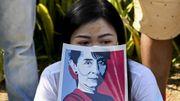 Une manifestante affiche le portrait d'Aung San Suu Kyi