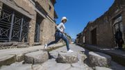 Female tourist jumping on stones in ruins of Pompeii, Naples, Italy