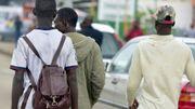 De jeunes hommes marchent dans le quartier populaire d'Abobo, à Abidjan, le 3 août 2017.