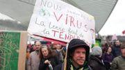 """""""Nous sommes le virus! La terre fait de la température"""" peut-on lire sur la pancarte de ce manifestant."""