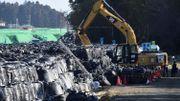 Des ouvriers emploient une grue de chantier pour empiler des sacs de déchets radioactifs le 12 février 2016 à Tomioka (Fukushima).