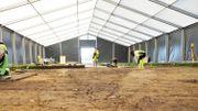 La gigantesque tente grise et blanche plantée en plein champ, où se déroulent les fouilles