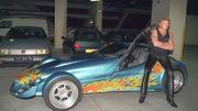 Le chanteur de rock et acteur français Johnny Hallyday pose pour les photographes, le 11 septembre 1995 dans le parking du Palais Omnisport de Paris-Bercy (POPB), aux côtés de la Vertigo dont il vient de faire l'acquisation.