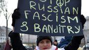 """Une manifestante brandit une pancarte sur laquelle on peut lire """"Stop au fascime et banditisme russe"""""""
