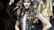Pauline Hoarau porte une coiffe ornée de plumes pour le défilé Etam.