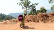 Une femme marche vers l'höpital de Panzi, portant ses affaires sur le dos