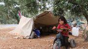 Un enfant syrien qui a fui les tirs d'obus des forces du régime et de leurs alliés dans la province d'Idlib, dominée par les djihadistes, joue près d'une tente dans une oliveraie où se sont réfugiées des familles déplacées, près du village d'Aqrabat, dans le district de Harem, dans la même province. frontière avec la Turquie le 31 mai 2019.