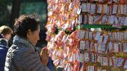 Une Coréenne prie pour le succès des étudiants qui passent des examens