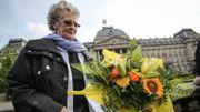 Une femme dépose des fleurs en hommage au roi Albert II