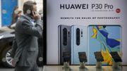 Un piéton passe devant un panneau publicitaire d'Huawei dans le centre de Londres le 29 avril 2019