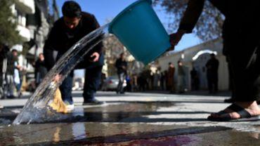 Des habitants de Kaboul nettoient la route après le double assassinat des juges de la Cour suprême Zakia Herawi et Qadria Yasini