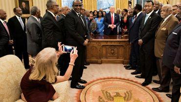 La conseillère du président américain Donald Trump, Kellyanne Conway (g), agenouillée sur un sofa pour prendre une photo du président avec des dirigeants de lycées et d'universités historiquement noirs, le 27 février 2017 dans le Bureau Ovale de la Maison Blanche