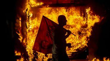 Un homme porte un drapeau à l'effigie de l'ex-président Luis Inacio Lula da Silva (2003-2010) devant un bus en flammes en marge de la manifestation en défense de l'université au Brésil, à Rio de Janeiro le 15 mai 2019