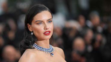 Adriana Lima a joué le contraste entre sa robe immaculée et ce collier type plastron bleu saphir, assorti à des boucles d'oreilles, prêtés par Chopard. Cannes, le 16 mai 2018.