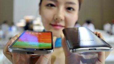 Une femme présente les nouveaux modèles de smartphone Samsung, à écran incurvé, le 10 octobre 2013 à Séoul