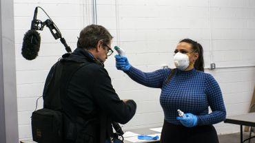 Une employée prend la température d'un journaliste américain alors que le maire de New York, Bill de Blasio, visite le Brooklyn Navy Yard.