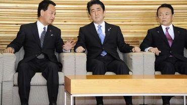 Le Premier ministre japonais Shinzo Abe (c), le ministre de la Revitalisation économique, Akira Amari (g) et le ministre des Finances, Taro Aso, le 18 novembre 2014 à Tokyo
