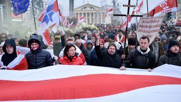 Les manifestants portent un drapeau biélorusse historique blanc-rouge-blanc géant et des bannières anti-intégration alors qu'ils assistent à un rassemblement de l'opposition contre un projet d'intégration biélorusse-russe à Minsk