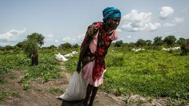 Au Soudan du Sud, une femme ramasse un sac de céréales distribué par le Programme alimentaire mondial, en juillet 2018