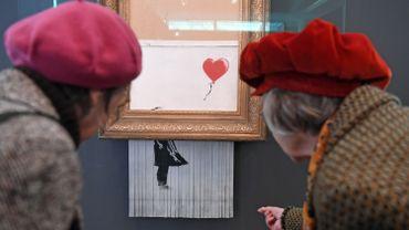 """L'oeuvre, désormais l'une des plus célèbres de l'artiste anonyme, montrait une petite fille lâchant un ballon rouge en forme de cœur et s'intitulait """"Girl with balloon"""" (""""Fille avec ballon""""). Depuis, Banksy la renommée """"Love is in the bin."""""""
