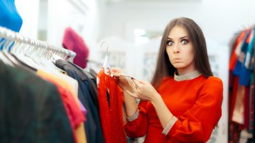 Surprised  Woman Checking Price Tag on a Dress in Sale Season