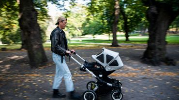 Un homme promène son bébé dans une poussette à Humlegarden à Stockholm le 24 septembre 2020.