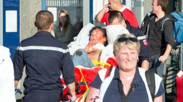 Un blessé est emporté de la gare d'Arras vers l'hôpital, vendredi soir.