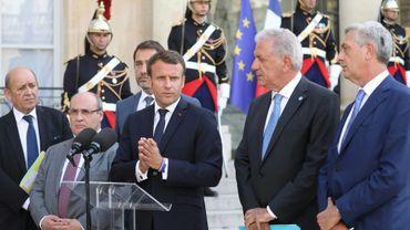 Emmanuel Macron (C) aux côtés notamment du directeur général de l'ONU pour les migrations, Antonio Manuel de Carvalho Ferreira Vitorino (2eG), du commissaire européen pour les migrations, Dimitris Avramopoulos (2eD) et du haut commissaire de l'ONU pour les réfugiés, Filippo Grandi (D), le 22 juillet 2019 à Paris
