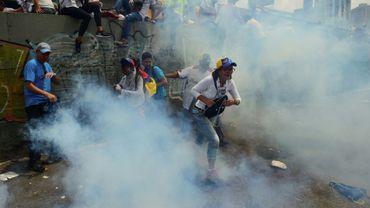 Des manifestants opposés à Nicolas Maduro courent se mettre à l'abri de gaz lacrymogène le 19 avril 2017 à Caracas