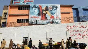 Des vendeurs de rue et des passants devant le cinéma Shama à Peshawar, le 19 décembre 2013