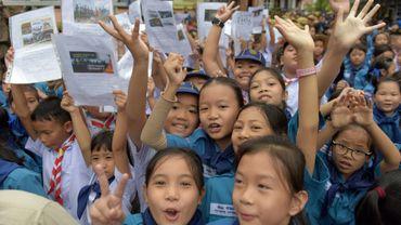 De jeunes Thaïlandais se réjouissent à Chiang Rai le 11 juillet 2018 en brandissant les portraits de douze jeunes footballeurs et leur entraîneur qui ont pu être évacués après être restés bloqués 18 jours dans une grotte