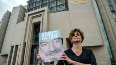 Une journaliste pose avec le portrait d'Ahmet Altan devant le tribunal d'Istanbul, le 19 juin 2017