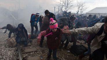 Des réfugiés s'enfuient après des tirs de gaz lacrymogènes par la police macédonienne le 29 février 2016 à la frontière avec la Grèce.