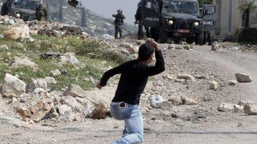 Un Palestinien jette une pierre sur des soldats israéliens pour protester contre l'expropriation de Palestiniens