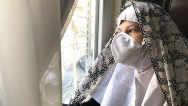 Une femme iranienne avec un masque à la maison, pendant la quarantaine liée au coronavirus.