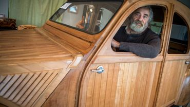 Michel Robillard, au volant de la 2 CV en bois grandeur nature dont il vient de terminer la fabrication, à Loches (centre de la France) le 20 mars 2017