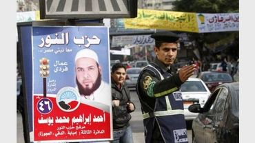 Un policier fait le trafic devant le panneau d'un candidat aux élections législatives égyptiennes, le 13 décembre 2011 au Caire
