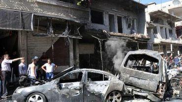 Des Syriens inspectent les lieux d'un attentat à la voiture piégée, le 25 juillet 2013 à Jaramana, dans la banlieue de Damas